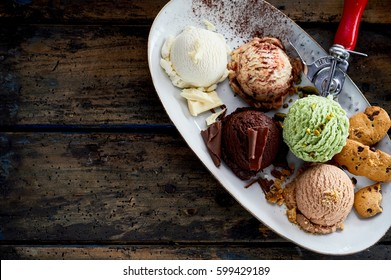 High Angle Still Life of Platter with Scoops of Delicious and Gourmet Ice Cream with Garnishes on Rustic Wooden Table Surface with Copy Space