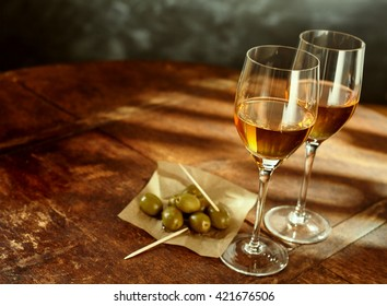 High Angle Still Life of Two Glasses of Warm Sherry Wine on Rustic Wooden Table with Green Olives and Picks