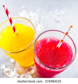 High Angle Still Life View of Refreshing and Colorful Frozen Fruit Slush Granita Drinks - Yellow and Red - in Glasses with Patterned Straws on Cold Metal Surface with Copy Space