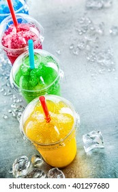 High Angle Still Life View of Colorful Frozen Fruit Slush Granita Drinks in Plastic Take Away Cups with Lids and Drinking Straws Arranged in Row on Cold Metal Surface with Ice Cubes and Copy Space