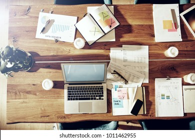 High angle of a table in an office with a laptop, takaway coffee cups and covered in paperwork