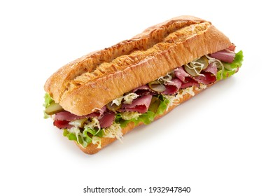 High angle of tasty baguette sandwich with ham slices and fresh vegetables on white background