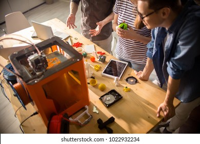 High angle of three creative designers working with 3D printer and discussing project plans standing round table with sample plastic models