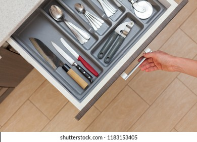 High angle top view cropped photo of woman hand open kitchen drawer by door handle, with different cutlery spoon, pizza knife, fork and stuff