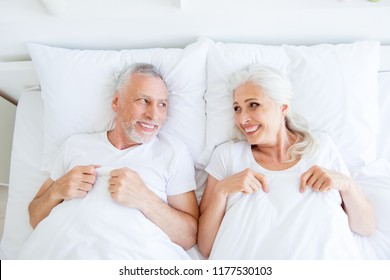 High angle top view of dreamy, couple in pajama, sleep, wear, sleepwear, nightwear with gray hair lying in the bed linen, sheets under blanket to look at each other in bright white interior