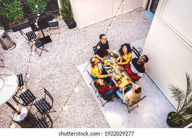 High angle top view of happy friends drinking cocktails and having fun at restaurant garden party - Food and beverage life style concept with young people together at home patio - Dark warm filter