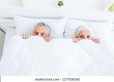 High angle top view surprised funny couple gray hair people in pajama, sleep, wear, sleepwear, nightwear with big eyed lying in the bed linen, sheets hiding themselves under blanket