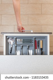 High angle top view vertical photo of cropped woman hand open new kitchen drawer by modern door handle, with different cutlery spoon, pizza knife, fork and stuff