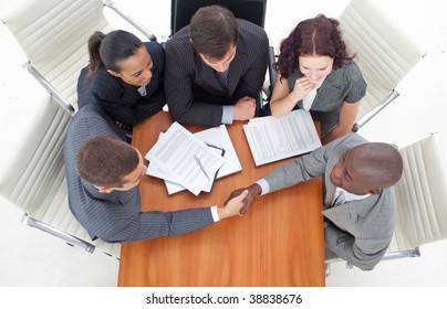 High angle of two businessmen shaking hands in a meeting. Agreement in  business