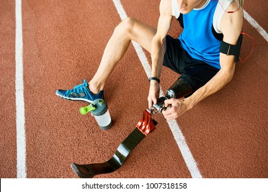High angle of unrecognizable amputee athlete fixing prosthetic leg sitting on running track in modern stadium