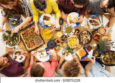 High angle of vegan friends eating a healthy dinner with hummus