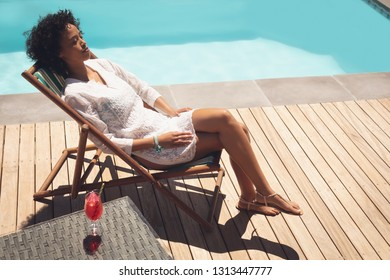 High angle view of African American woman relaxing on sun lounger in her backyard on a sunny day