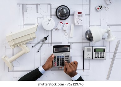 High Angle View Of Architect Hands Using Calculator Working On Blueprint With Security Equipments