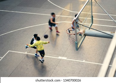 High angle view of Asian children playing basketball outdoors at sunset