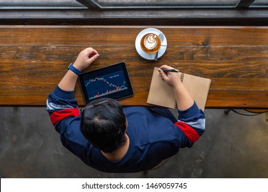 High angle view of Asian investor checking stock market on tablet