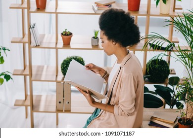 high angle view of attractive african american businesswoman reading documents in office