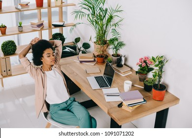 high angle view of attractive african american businesswoman resting on chair in office