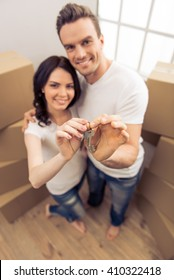 High angle view of attractive young couple moving, holding keys, hugging, looking at camera and smiling while standing among cardboard boxes