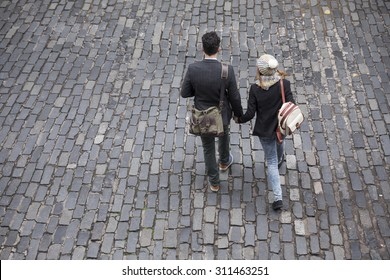 High angle view of the back of a couple walking down the street. Young man and woman walking together.