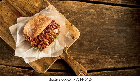 High angle view of baked bread roll with meat prepared on cutting board against wooden table