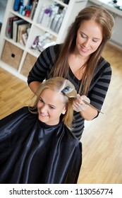 High angle view of beautician applying hair dye on female customer's hair - shallow DOF focus on hair stylist