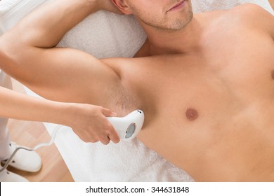 High Angle View Of Beautician Giving Laser Epilation Treatment On Man's Armpit