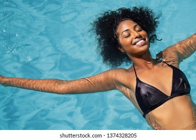 High angle view of beautiful african american girl with curly hair and bikini floating on back in swimming pool. Top view of smiling young woman carefree in pool with eyes closed relaxing in pool.