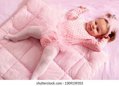 High angle view of a beautiful baby girl wearing pink tutu skirt lying on a  pink 266a71938211