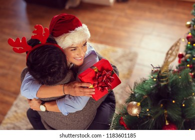 High angle view of a beautiful couple in love, wearing santa hats, standing next to a nicely decorated Christmas tree, exchanging Christmas presents and hugging