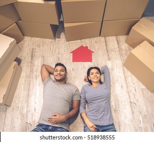 High angle view of beautiful couple smiling while lying on the floor near the moving boxes