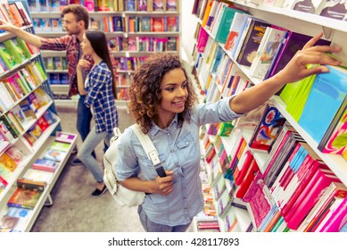 High angle view of beautiful female student smiling while choosing book at the bookshop, young man and girl in the background