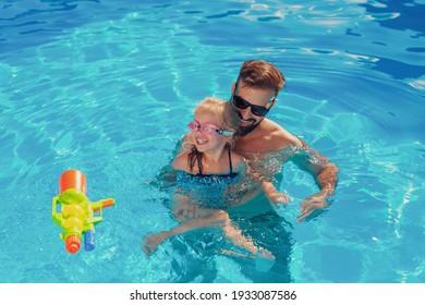 Schöne Aussicht auf das schöne kleine Mädchen und ihren Vater, die sich an einem sonnigen Sommertag im Schwimmbad amüsieren, Vater lehrt Tochter schwimmen