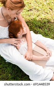 high angle view of beautiful redhead mother and daughter with book sitting at park
