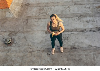 High angle view of a beautiful young woman standing on a building rooftop terrace, taking a workout break and eating banana