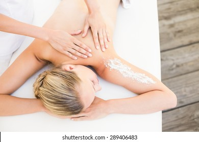 High angle view of a beautiful young woman lying on massage table at spa center
