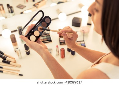 High angle view of beautiful young woman doing makeup using eyeshadow, sitting in front of the mirror