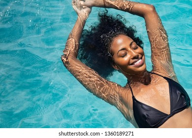 High angle view of black woman relaxing in the water with closed eyes. Portrait of happy woman in bikini floating in a water. Top view of relaxed african girl in swimming pool with copy space.