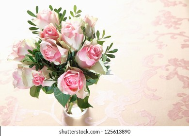 High angle view of a bouquet of fresh pink roses with greenery arranged in a glass vase with copyspace