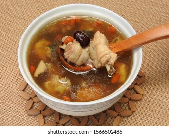High angle view of a bowl of chicken soup on bamboo mat. It contain Chinese medicine such as goji berry and red jujube. Warm, and nutritious . Good for health. Taiwan food and winter food concept.
