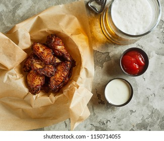High angle view of bowl with fried chicken wings,  served with sauces and glass of beer