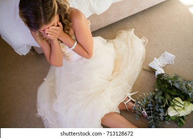High angle view of bride in wedding dress crying while sitting by bed at home