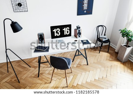 High angle view of a bright home office interior for a creative professional with black and white furniture and herringbone parquet floor. Real photo.
