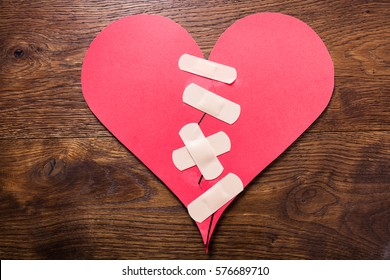 High Angle View Of A Broken Heart Fixed With Bandage On Wooden Desk