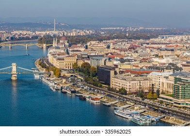 High angle view of Budapest during the day in the autumn. Parliament, the Chain Bridge, buildings and boats can be seen.