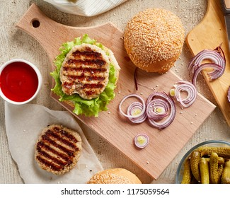 High angle view of burger on wooden board with onion and tomatoes