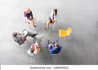 High angle view of business colleagues planning while sitting at office during meeting