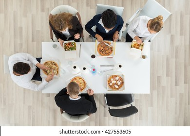 High Angle View Of Business Colleagues Eating Food Together In Office