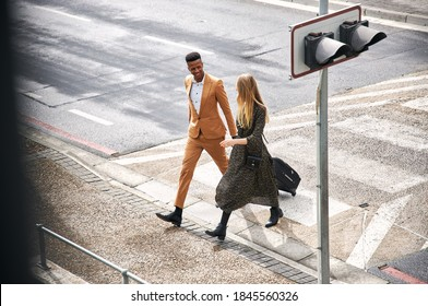 High Angle View Of Business Couple Crossing Street On Way To Meeting