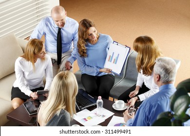High angle view of business people sitting at meeting. Executive businesswoman presenting her idea to sales team while they are on staff meeting at office. Teamwork.