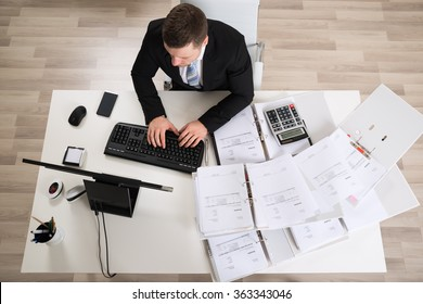 High angle view of businessman analyzing documents at computer desk in office